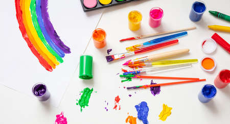 Foto de Kids creativity, rainbow drawing. Colorful finger paints set and paint brushes on white color background, top view - Imagen libre de derechos