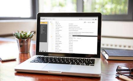 Photo pour Email inbox message list on a computer laptop screen, office wood desk, business background. E-mail correspondence mail concept - image libre de droit