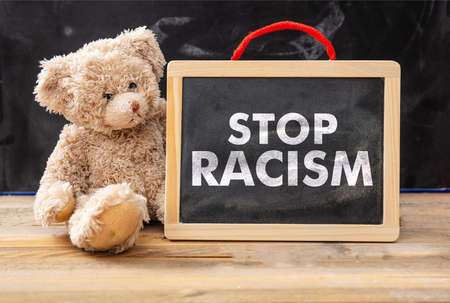 Photo pour Stop racism and kids concept. Teddy bear and a board with Stop racism text, school class blackboard background. No to racism for children message. - image libre de droit