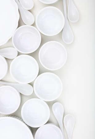 Photo pour Dishware concept. White empty porcelain bowls and teaspoons background. Clean, new, luxury soup pots and spoons, vertical photo.  - image libre de droit