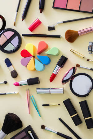 Photo for Make up cosmetics flat lay. Lipstick and nail polish, eye shadows and blush, brushes and pencils against yellow color background, top view - Royalty Free Image