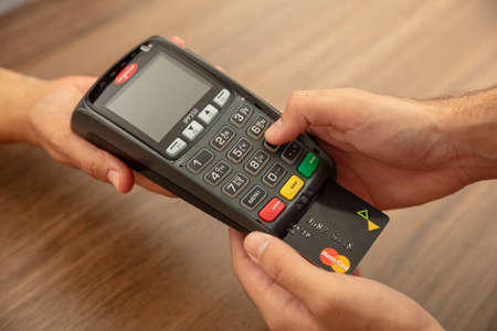Photo pour Athens, Greece. June 27, 2020. Wireless POS payment terminal Ingenico with credit card Mastercard isolated on white background, close up view. - image libre de droit