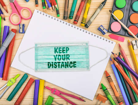 Photo pour KEEP YOUR DISTANCE text message on a medical protective mask, school supplies flat lay, Back to school, coronavirus days - image libre de droit