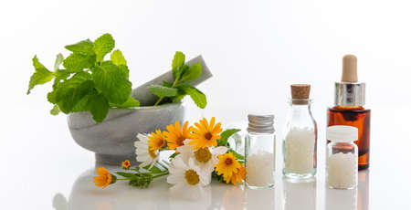 Foto de Alternative herbal medicine. Homeopathic globules, fresh wild flowers and herbs isolated against white background. Aromatherapy, Homeopathy natural products - Imagen libre de derechos
