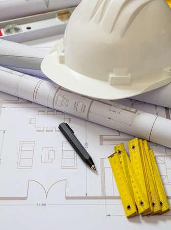 Photo pour Project blueprints and engineer hardhat white color on drawings background. Housing project construction, architect site office concept. - image libre de droit