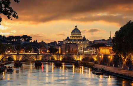 Foto de Rome Italy. Saint Peter Basilica in the Vatican over illuminated Sant Angelo bridge and Tiber river night view, orange color sky after sunset - Imagen libre de derechos
