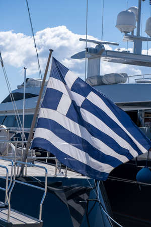 Photo pour Greek flag on a luxury boat anchored in a marina in Greece. Blue white color flag waving on yacht stern. Blue sky background, close up view. - image libre de droit