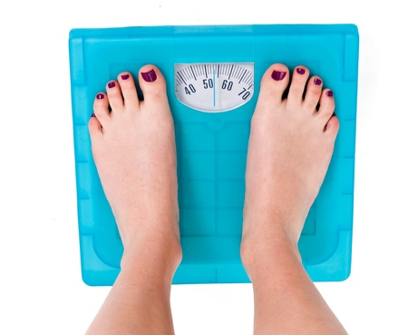 Foto de Woman on weight scale on isolated background  - Imagen libre de derechos
