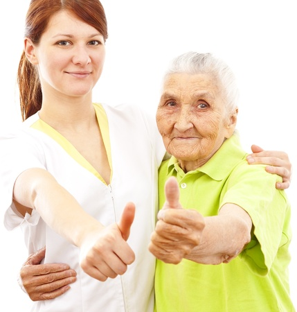 a young female doctor and a very old woman showing thumbs up
