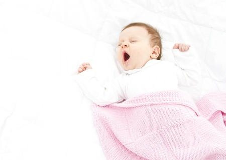 adorable gapy baby ona white bed witha  pink blanket
