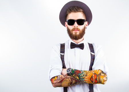 young hipster man wearing  hat, suspenders,  bow-tie and a funny tattoo-sleeve