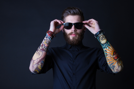 Foto de portrait of a hipster man wearing colourful tattooes on his arms posing over a  black background - Imagen libre de derechos