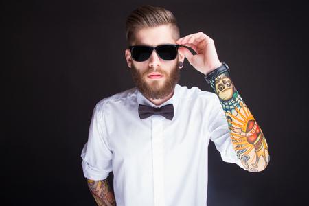 Foto de studio portarit of  ayoung fashionable hipster man in white shirt posing over a black background - Imagen libre de derechos