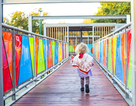 Happy little child running in the playground.