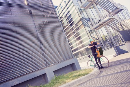 Photo pour Bike messenger with orange backpack in the city - image libre de droit