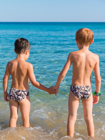 Two children holding hands in beach in front of sea