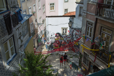 Typical Corner of Lisbon with Traditional Houses, Azulejos, Stairs, Colorful Walls and Couple of Tourists