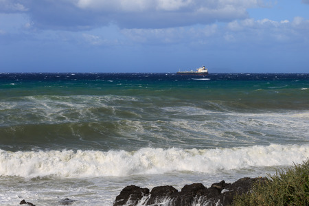 Large Container Ship Near Coastline in Windy Day: Stormy Weather.