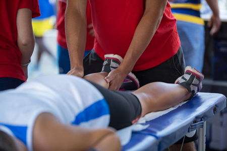 Foto de Athlete lying on a Bed while having Legs Massaged after a Physical Sports Workout. - Imagen libre de derechos