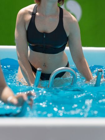Photo pour Girl Doing Water Exercises with Bike Outdoor in a Swimming Pool. - image libre de droit