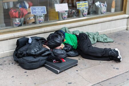 Photo for Street Photography: Homeless Sleeping on the Street in front of a Store Window. - Royalty Free Image