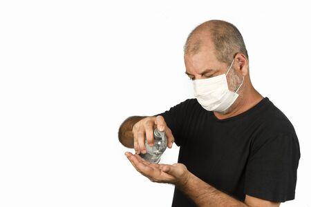Retrato de um homem, em uma máscara médica usando gel de álcool. Um conceito do perigo do coronavírus COVID-19 para idosos. sobre fundo branco, com espaço para texto
