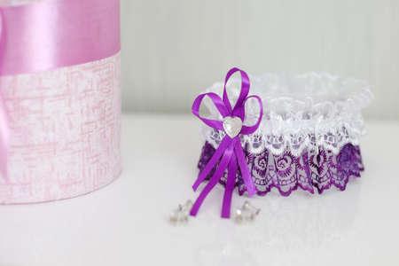 Foto de Wedding purple garter and flowers on a white table - Imagen libre de derechos