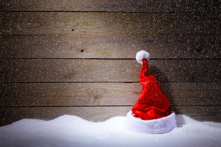 Santa hat in snow on wooden background with snowfall.