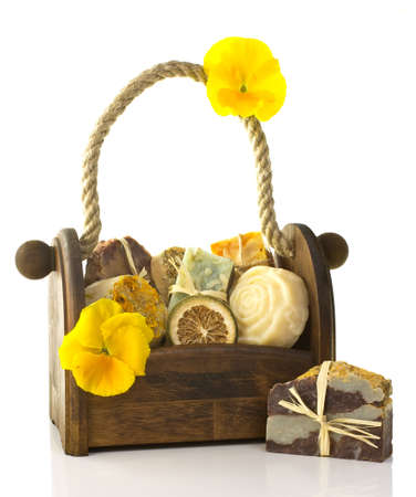 Composition of the basket full of handmade soap, isolated on white background.
