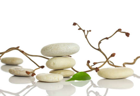 Spa stones and green leaf, isolated on white background
