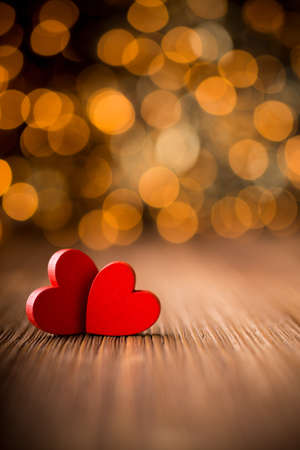 Hearts on a wooden table and background is a bokeh