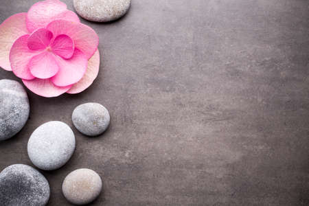 Close up view of spa stones and flower on grey background.