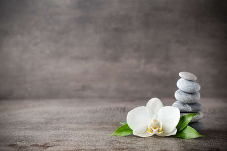 Spa stones and white orchid on the grey background.