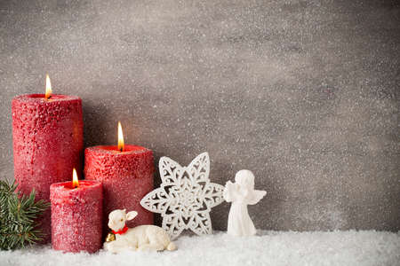 Three red candles on gray background, Christmas decoration. Advent mood.