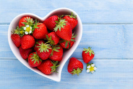 Photo pour Strawberry heart. Fresh strawberries in plate on white wooden table. Top view, copy space. - image libre de droit