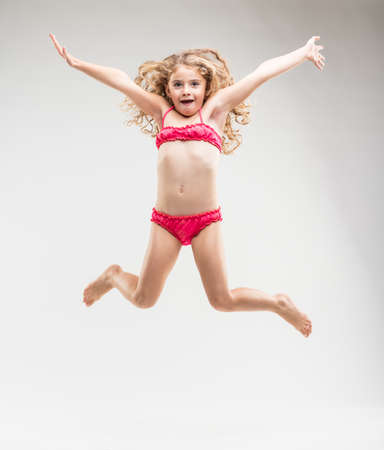Agile exuberant little girl with long curly blond hair in a pink bikini leaping in the air with outspread arms as she grins happily at the camera isolated on white