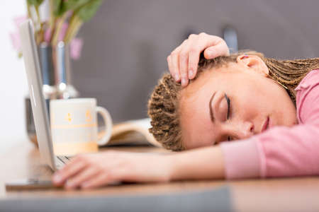 Tired attractive young woman sleeping on a table or desk with her hand looped over her head and eyes closed in a serene expression in a low angle view