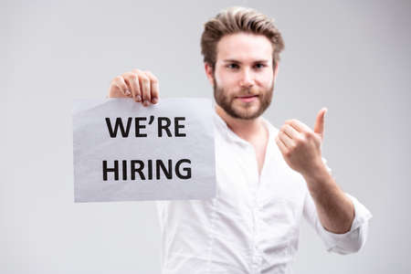 Employment concept - We Are Hiring - with an attractive young man with a beard holding up a sign and giving a thumbs up of approval or success