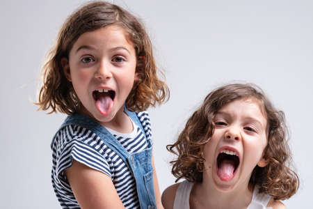 Photo pour Playful little girls sticking out their tongues at the camera as they stand stand by side on a white background - image libre de droit