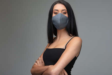 Photo pour Confident attractive woman wearing a stylish fashionable protective face mask posing with folded arms on grey in a concept of adapting to post coronavirus fashion and lifestyle - image libre de droit