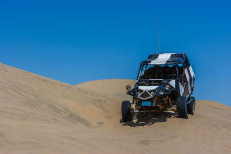 Photo pour Dune buggy over a sand dune with blue sky in the desert, Huacachina, Ica, Peru - image libre de droit