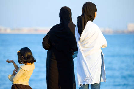 Doha,  Qatar - April 10, 2006: Women in traditional dress  looking at the sea from the La Corniche waterfront