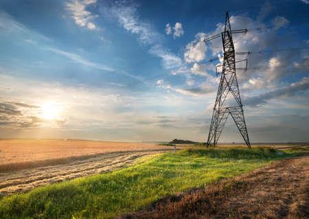Photo pour Electric pole in the autumn field at sunrise - image libre de droit