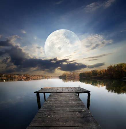 Fishing pier on a river under fool moon. Elements of this image furnished by NASA