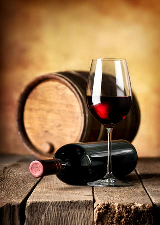 Red wine and wooden cask on a table