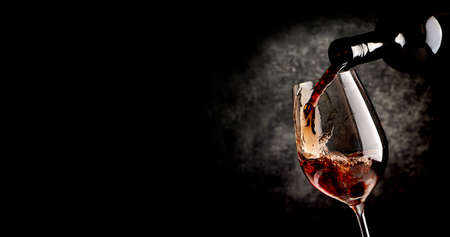 Photo for Wine pouring in wineglass on the black background - Royalty Free Image