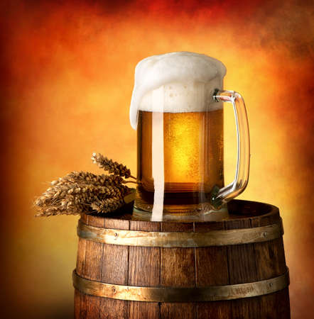 Photo pour Glass of lager and wheat on a wooden barrel - image libre de droit