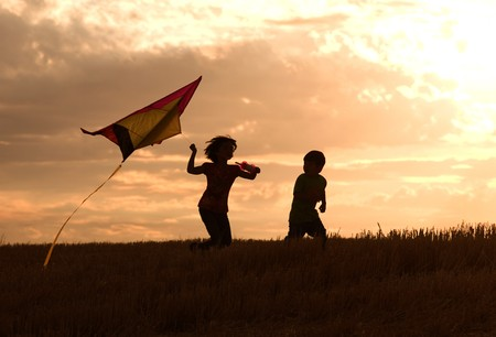 Two kids flying a kite at sunset invoke childhood memories.