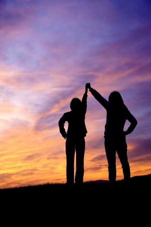 A mother and daughter holding raised hands watch the sunset