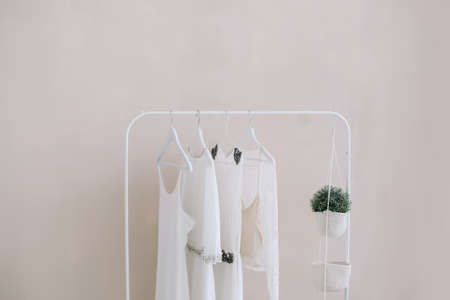 Foto de White dresses on a hanger. Set of women wedding dresses on a wooden hangers, fashion background, close up - Imagen libre de derechos